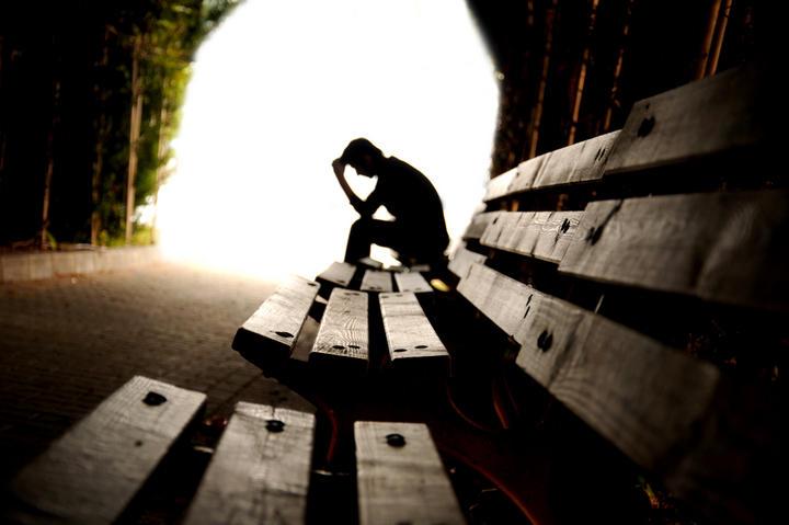 Homem solitário sentado num banco